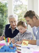 Boy Drawing With Crayons With Father And Grandfather - stock photo