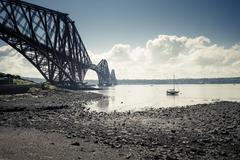 Stock Photo of Great Britain, Scotland, Forth Bridge South, low tide and sailboat