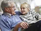 Stock Photo of Girl With Grandfather Reading Story Book
