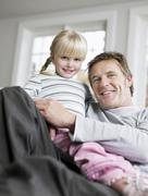 Girl Sitting On Father's Lap In House Stock Photos