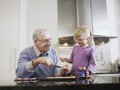 Girl And Grandfather Eating Breakfast Stock Photos