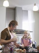 Stock Photo of Girl And Father Baking In Kitchen