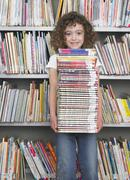 Girl Holding Stack Of Books In Library - stock photo