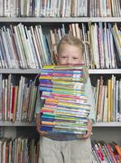 Girl Carrying Stack Of Books In Library - stock photo