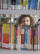 Girl Selecting Books From Library Bookshelf - stock photo
