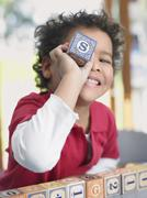 Boy Playing With Alphabet Block In Class - stock photo