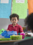 Boy Looking Into Lunchbox In Class Stock Photos