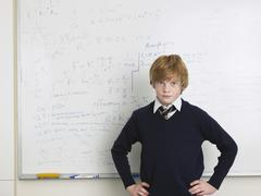 Student Standing By Whiteboard In Math Class - stock photo