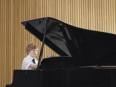 Poika pelaaminen Piano In Music Class Kuvituskuvat