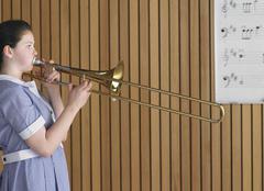 Tyttö pelaaminen pasuuna In Music Class Kuvituskuvat