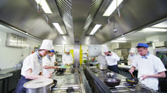 Stock Video Footage of Team of professional chefs preparing and cooking food in a commercial kitchen