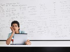 Stock Photo of Man Bored With Laptop In Classroom