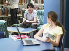 Stock Photo of Boy Looking At Girl In Library