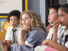 Thoughtful Students Sitting In Classroom Stock Photos
