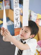 Boy Learning To Read From Hanging Paper Strip In Class Stock Photos