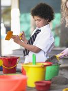 Boy Playing In Sand Pit In School Playground Stock Photos