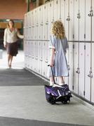 Girl Walking Towards Mother In School Corridor - stock photo
