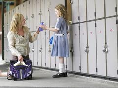 Mother Packing Daughter's School Bag Stock Photos