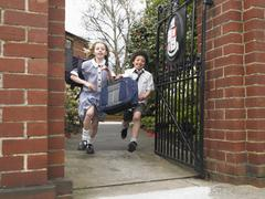 Stock Photo of Students Running Out Through School Gate