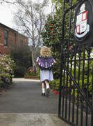Stock Photo of Small Girl Running Out Of The School Gate