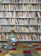 Boy Reading Book In Library - stock photo