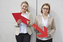 Germany, Businesswomen holding arrows pointing in opposing directions - stock photo