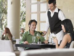Waiter Serving Wine To Couple - stock photo