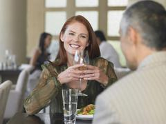 Stock Photo of Woman Smiling At Man Over Meal In Restaurant