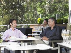 Businessmen Conversing At Outdoor Cafe - stock photo
