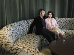 Couple Sitting On Couch In Hotel Lobby Stock Photos