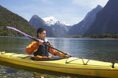 Man Kayaking In Mountain Lake - stock photo