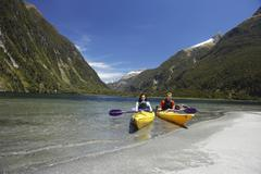 Two People Kayaking In Mountain Lake - stock photo