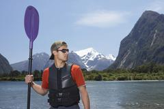 Man With Oar In Front Of Mountain Lake - stock photo