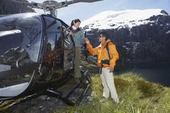 Hikers With Helicopter On Mountain Top - stock photo