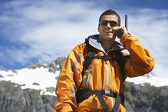 Man Using Walkie Talkie Against Mountain - stock photo