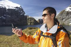 Hiker Using Compass By Mountain Lake Stock Photos