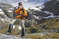 Hiker Using Cellphone With Walking Stick In Mountains Stock Photos