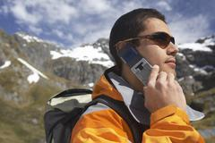 Male Hiker Using Cellphone Against Mountains Stock Photos