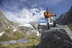 Hiker On Top Of Boulder In Mountains Stock Photos