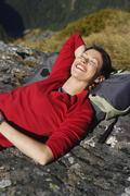 Happy Woman Lying On Boulder With Backpack - stock photo