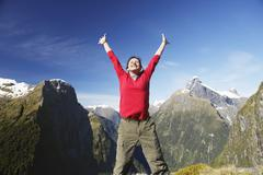 Stock Photo of Woman Raising Arms Against Mountain Peaks