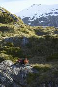 Hikers Sitting On Boulders In Mountain Valley - stock photo