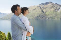 Romantic Couple Looking At Mountain Lake Stock Photos
