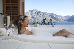 Woman In Bubble Bathtub With Mountain Lake Outside Window - stock photo