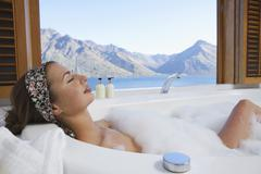 Stock Photo of Woman In Bubble Bathtub With Mountain Lake Outside Window