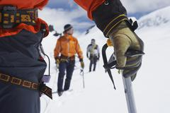 Hikers Using Walking Sticks In Snowy Mountains Stock Photos