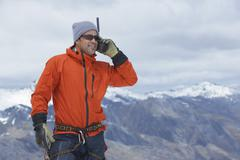 Hiker With Walkie Talkie Against Mountain Peak Stock Photos