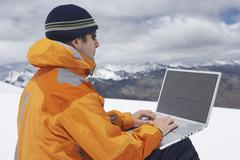 Hiker Using Laptop On Snowy Mountain Landscape - stock photo