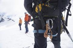 Backpack And Safety Ropes In Snowy Mountains With Two Friends Ahead - stock photo