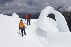 Hikers By Ice Formation In Mountains - stock photo